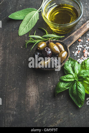 Green and black Mediterranean olives with fresh herbs - Stock Photo