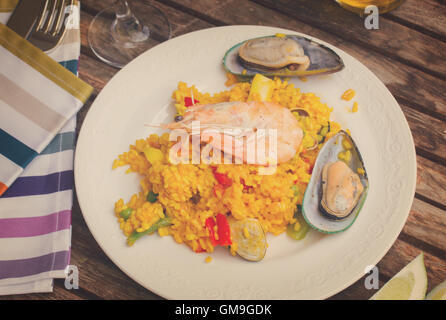 Paella served in plate on wooden table - Stock Photo