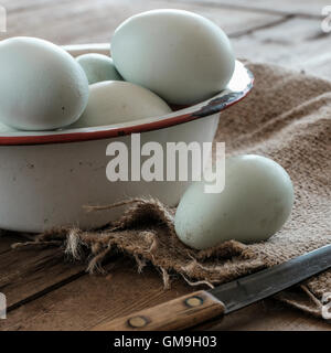 Fresh eggs in bowl on wooden table - Stock Photo