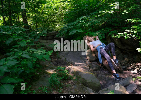 Woman lying on stone in forest - Stock Photo