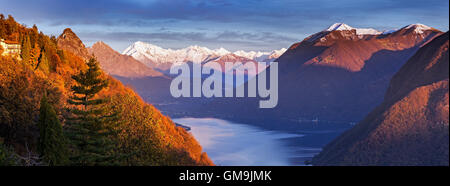Switzerland, Lugano, Horizontal panorama of mountains and lake at sunset - Stock Photo