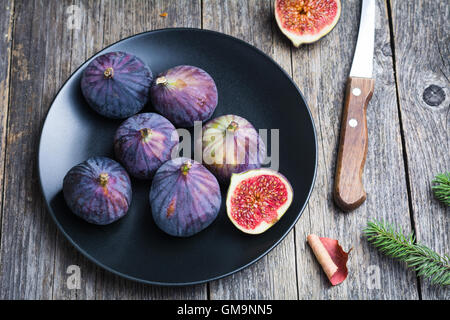 Fresh figs on black plate on wooden table - Stock Photo