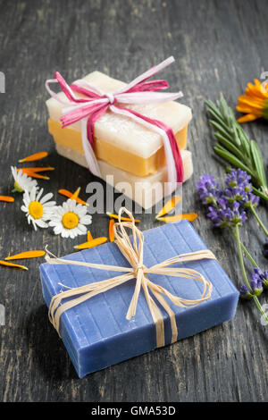 Colorful handmade soaps with fresh herbs on rustic wooden background - Stock Photo