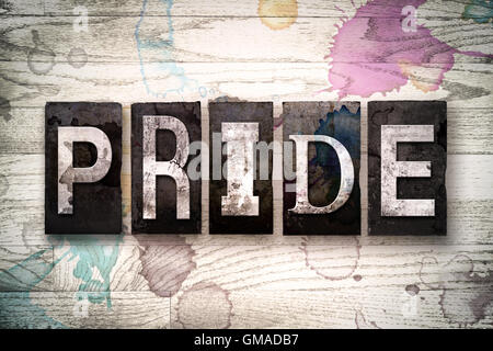 The word 'PRIDE' written in vintage dirty metal letterpress type on a whitewashed wooden background with ink and - Stock Photo