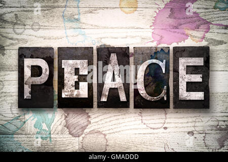 The word 'PEACE' written in vintage dirty metal letterpress type on a whitewashed wooden background with ink and - Stock Photo