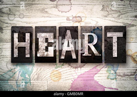 The word 'HEART' written in vintage dirty metal letterpress type on a whitewashed wooden background with ink and - Stock Photo