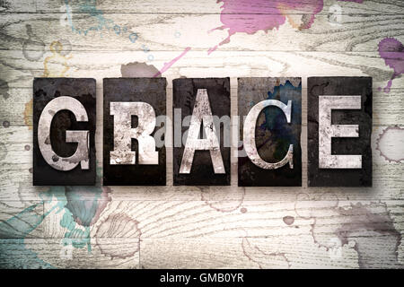 The word 'GRACE' written in vintage dirty metal letterpress type on a whitewashed wooden background with ink and - Stock Photo