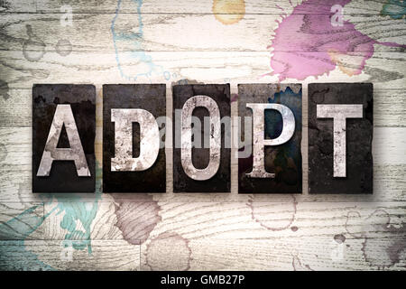 The word 'ADOPT' written in vintage dirty metal letterpress type on a whitewashed wooden background with ink and - Stock Photo