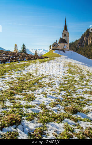 The church of the little village of Schmitten surrounded by snow Albula District Canton of Graubünden Switzerland - Stock Photo