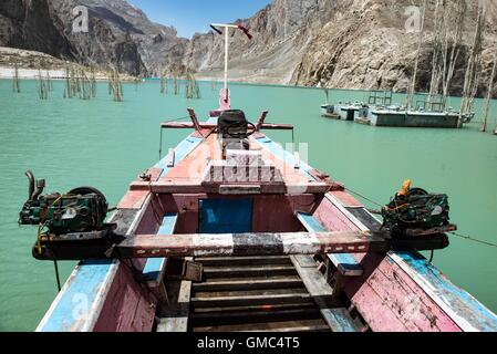 Redundant ferry boats and a pontoon on Attabad lake. The landslide that formed the lake is in the background. - Stock Photo