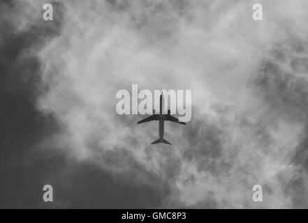 Civil aircraft cloud sky in black and white. - Stock Photo