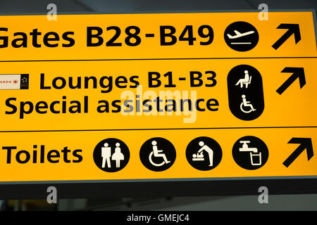 Sign pointing to the Special Assistance Lounges at Heathrow airport Terminal 2, & toilet / toilets / lavatories - Stock Photo