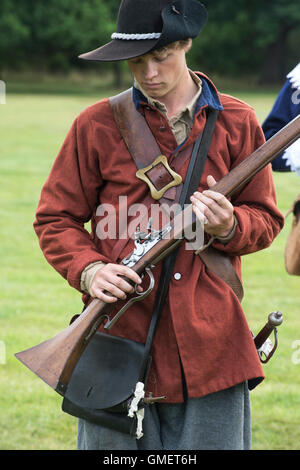 English Civil War Royalist soldier preparing his musket at a reenactment, Spetchley Park, Worcestershire, England - Stock Photo