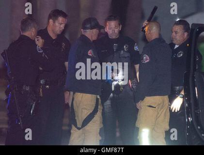 Huntington Beach, California, USA. 26th Aug, 2016. A Huntington Beach Police officer is checked out by Costa Mesa - Stock Photo