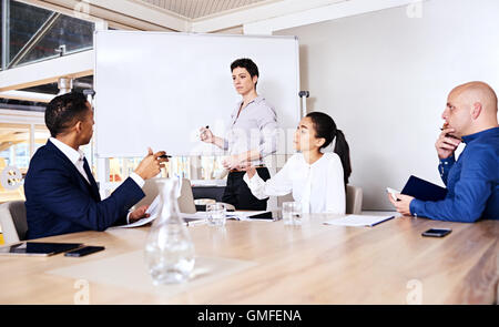 Mature woman giving a business presentation to three potential investors - Stock Photo