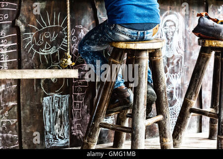 Man sitting at a bar on a barstool, Dominical village, Costa Rica, Central America - Stock Photo