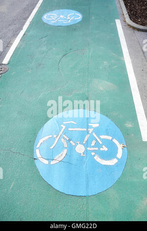 Bicycle path signs on a green painted road. - Stock Photo