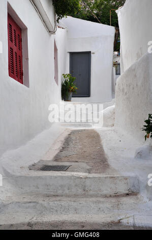 Houses and narrow street with steps painted white in the traditional Anafiotika neighborhood of Plaka, Athens Greece. - Stock Photo