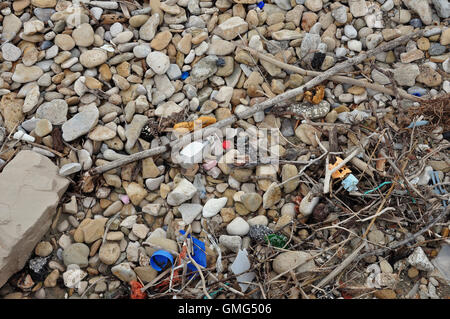 Plastic and driftwood washed ashore on stone beach. Coastal pollution. - Stock Photo