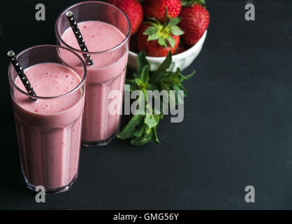 Strawberry and mint smoothie in tall glasses, bawl of fresh berries on dark rustic wood background - Stock Photo