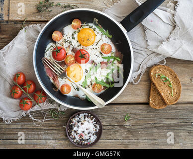 Pan of fried eggs, bacon and cherry-tomatoes with bread - Stock Photo