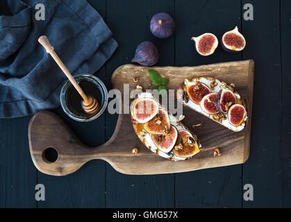 Sandwiches with ricotta, fresh figs, walnuts and honey on rustic wooden board - Stock Photo