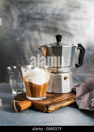 Glass of coffee with ice cream on rustic wooden board and steel Italian Moka pot - Stock Photo