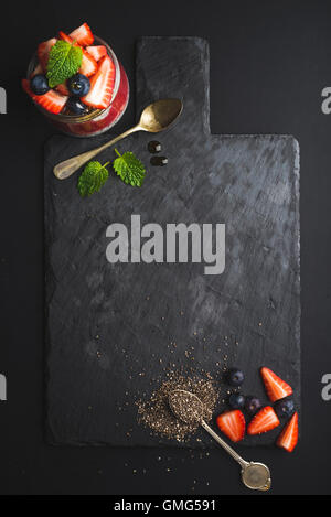 Healthy breakfast food frame. Chia pudding with fresh berries and mint on black slate stone board over dark background - Stock Photo