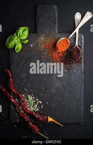 Herbs and spices on black slate stone board over dark background. - Stock Photo