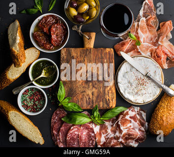 Wine snack set with empty wooden board in center. Glass of red, meat selection, mediterranean olives, sun-dried - Stock Photo