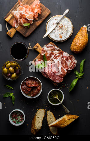 Wine snack set. Glass of red, meat selection, mediterranean olives, sun-dried tomatoes, baguette slices, camembert - Stock Photo