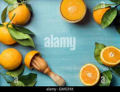 Fresh orange juice in glass and oranges with leaves on wooden turquoise blue painted background - Stock Photo