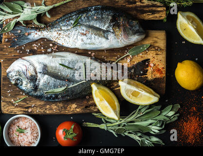 Fresh uncooked dorado or sea bream fish with lemon, herbs, oil, vegetables and spices on rustic wooden board over - Stock Photo
