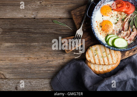 Breakfast set. Pan of fried eggs with bacon, fresh tomato, cucumber, sage and bread on rustic serving board over - Stock Photo