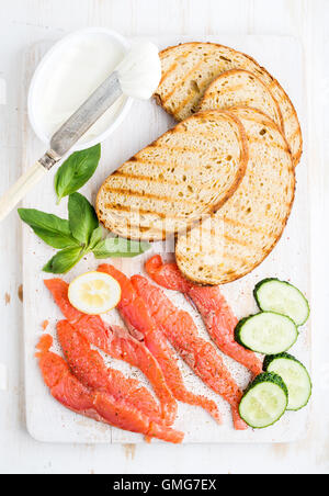 Ingredients for healthy sandwich. Grilled bread slices, smoked salmon, cottage cheese, cucumber nd basil on white - Stock Photo