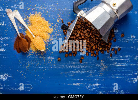 Arabika eans in moka pot,brown sugar and ground coffee on wooden blue painted table - Stock Photo