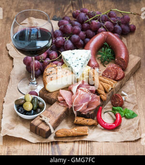 Glass of red wine, cheese and meat board, grapes,fig, strawberries, honey, bread sticks  on rustic wooden table, - Stock Photo