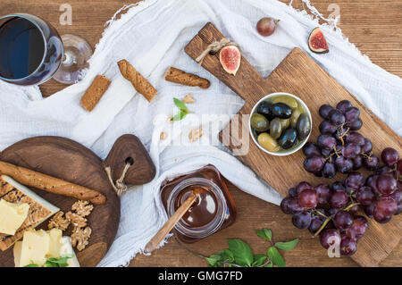 Glass of red wine, cheese board, grapes, walnuts, olives, honey and bread sticks - Stock Photo