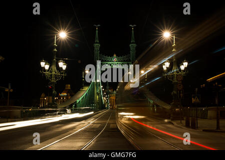 Night view of tram and cars crossing Liberty Bridge in Budapest, Hungary - Stock Photo