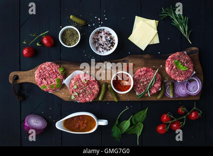Ingredients for cooking burgers. Raw ground beef meat cutlets on wooden chopping board, red onion, cherry tomatoes, - Stock Photo