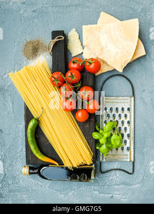 Ingredients for cooking pasta. Spaghetti, Parmesan cheese, cherry tomatoes, metal grater, olive oil and fresh basil - Stock Photo