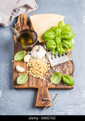 Ingredients for cooking Pesto sauce. Parmesan cheese, metal grater, fresh basil, olive oil, garlic and pine nuts - Stock Photo