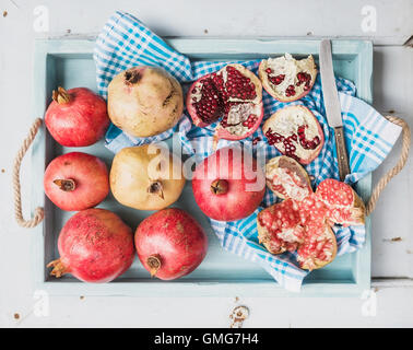 Red and white pomegranates with knife on kitchen towel in blue tray over light painted wooden backdrop - Stock Photo