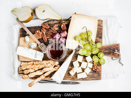 Cheese appetizer set. Various types of cheese, honey, grapes, pear, nuts and bread grissini sticks on rustic wooden - Stock Photo