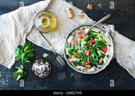 Spring salad with lamb's lettuce, grapefruit, garnet, walnuts and olive oil in vintage metal plate - Stock Photo