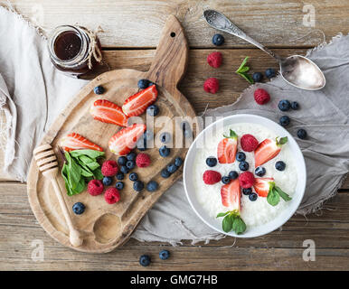 Healthy breakfast set. Rice cereal or porridge with berries and honey - Stock Photo
