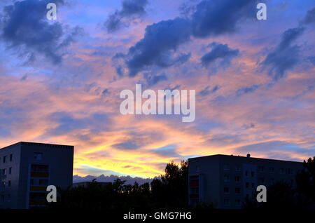 Red sunset sky with dramatic clouds over city of berlin - Stock Photo