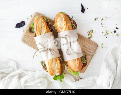 Sandwiches with beef, fresh vegetables and herbs on rustic wooden chopping board - Stock Photo