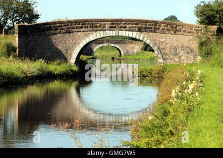 Two stone bridges reflected in the water as they cross the Leeds and Liverpool canal near Ollerton in Lancashire. - Stock Photo