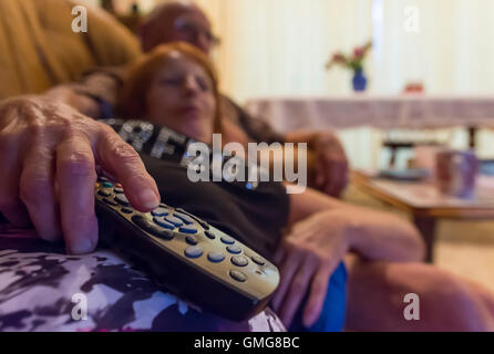 Elderly couple relaxing on a sofa in a living room watching TV. - Stock Photo